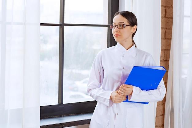 Mooie vrouwelijke arts in glazen met map die ergens in de buurt van het raam kijkt.