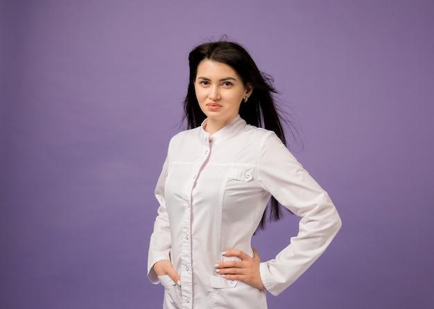 Mooie vrouwelijke arts in witte medische jurk op paars