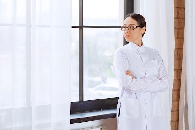 Mooie vrouwelijke arts met een bril die bij het raam staat en kijkt.