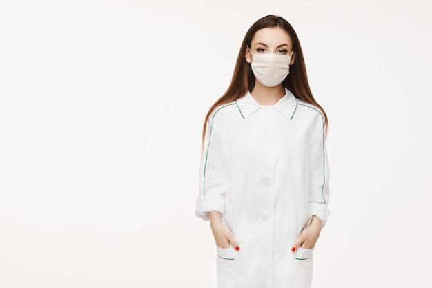 Mooie vrouwelijke arts of verpleegster die beschermend masker en het medische toga stellen dragen. jonge vrouw in medische uniform. gezondheidszorg concept