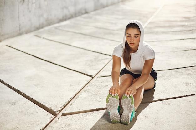 Mooie vrouwelijke atleet die zich uitstrekt vóór training buitenshuis. stedelijk sportconcept.