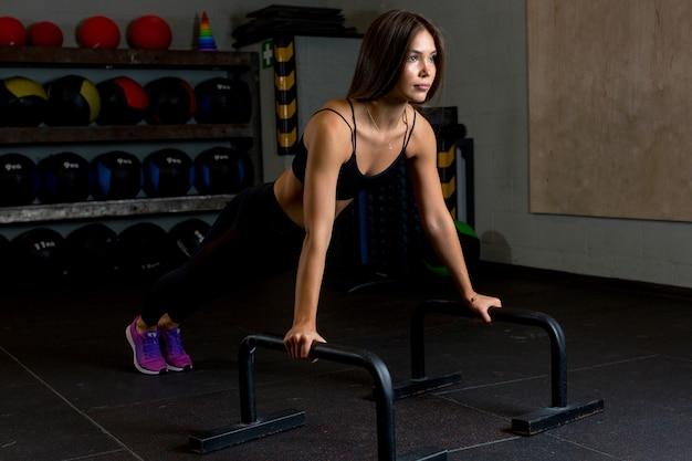 Mooie vrouwelijke atleet doet push-ups op metalen standaards om haar armen in de sportschool te versterken te midden van sportartikelen.