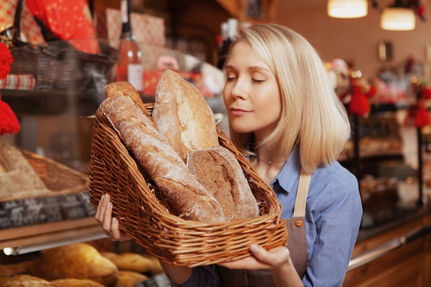 Mooie vrouwelijke bakker ruiken vers brood, genieten van het werken bij haar bakkerij-winkel