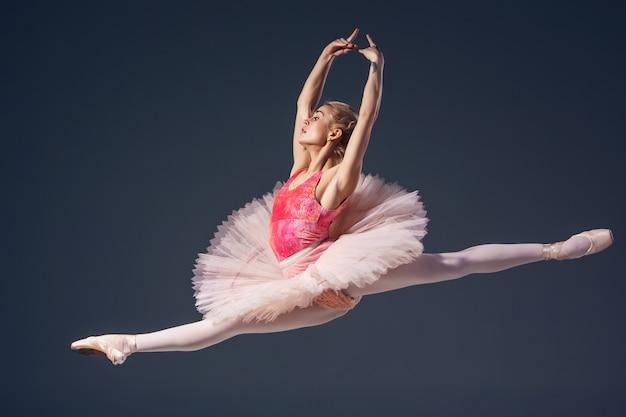 Mooie vrouwelijke balletdanser op een grijze achtergrond