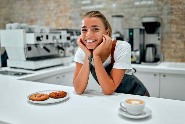 Mooie vrouwelijke barista bereidt een kopje koffie of cappuccino en een bord met koekjes voor een klant in een coffeeshop.