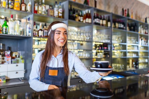 Mooie vrouwelijke barista houdt een kopje warme koffie vast en draagt een gezichtsscherm terwijl ze in de buurt van de bar in het café staat. nieuw normaal