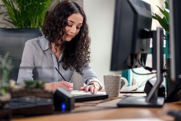Mooie vrouwelijke beambte schrijft iets aan de notebook. creatieve mensen of reclame bedrijfsconcept