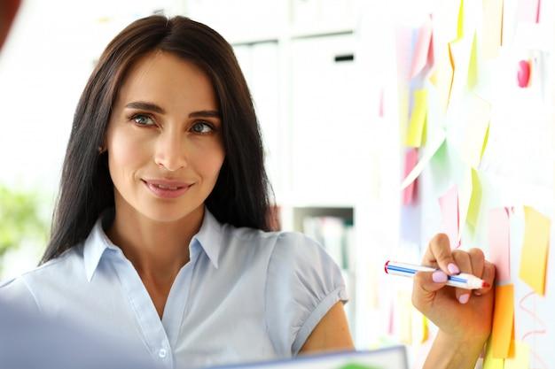 Mooie vrouwelijke bediende die iets op whiteboard trekt tijdens bedrijfsgesprek