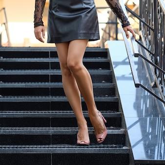 Mooie vrouwelijke benen die de trap aflopen