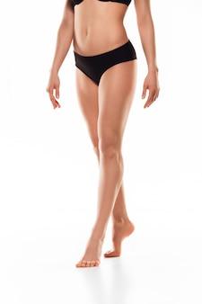 Mooie vrouwelijke benen die op wit worden geïsoleerd. schoonheid en fitness concept