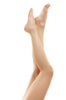 Mooie vrouwelijke benen die op wit worden geïsoleerd.