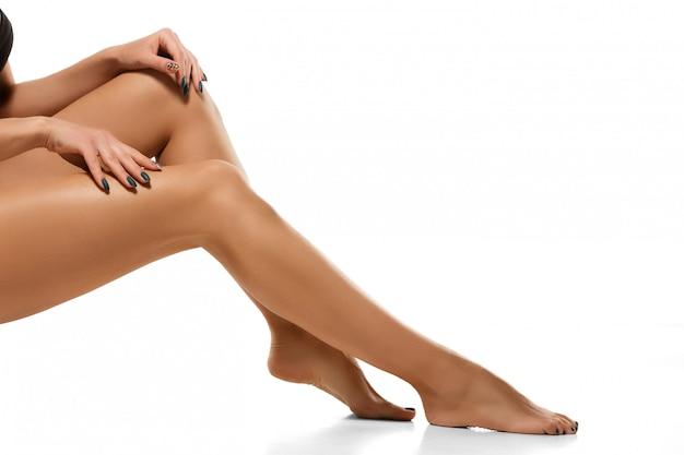 Mooie vrouwelijke benen die op wit worden geïsoleerd
