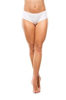Mooie vrouwelijke benen en buik geïsoleerd op een witte muur