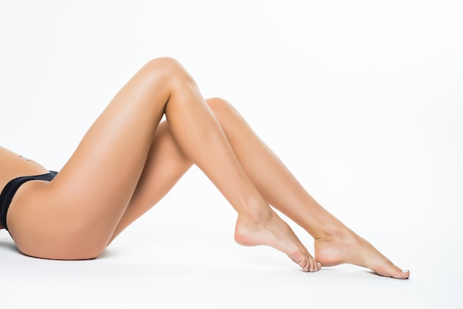 Mooie vrouwelijke benen, ezel achterlichaam dat over witte muur wordt geïsoleerd die op de vloer met lang been ligt, beauty spa en het concept van de huidzorg.
