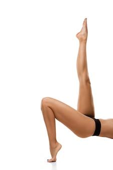 Mooie vrouwelijke benen geïsoleerd op een witte muur