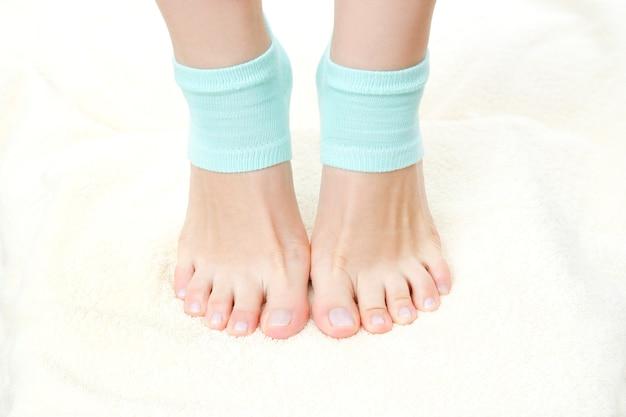 Mooie vrouwelijke benen in blauwe sokken voetverzorging sta op tenen