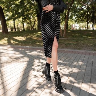 Mooie vrouwelijke benen in modieuze zwarte leren laarzen op een zonnige lentedag. mooi gestileerd meisje in een modieuze zwarte jurk en schoenen loopt in het park
