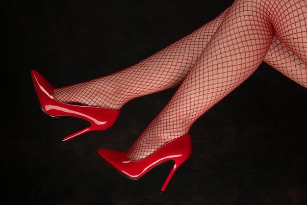 Mooie vrouwelijke benen in netkousen en rode schoenen