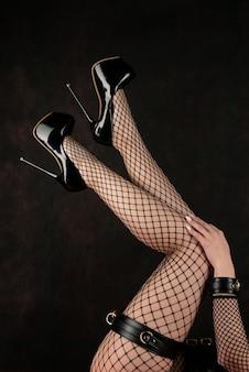 Mooie vrouwelijke benen in netkousen en zwarte schoenen