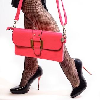 Mooie vrouwelijke benen in panty in het net en schoenen op rode stiletto's en roze clutches