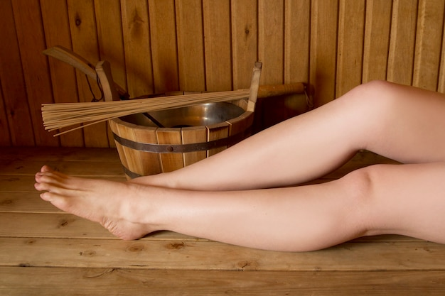 Mooie vrouwelijke benen in sauna, badaccessoires. houten emmer en stokken