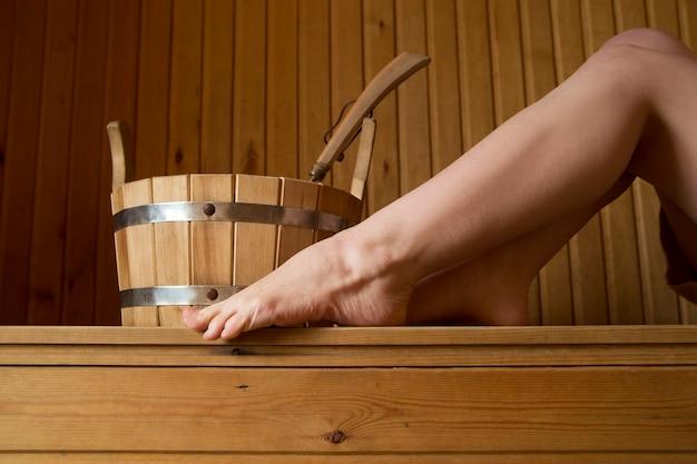 Mooie vrouwelijke benen in sauna, badaccessoires. houten emmer