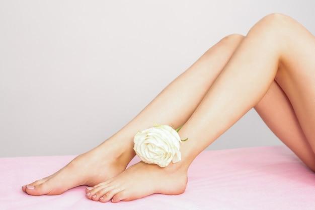 Mooie vrouwelijke benen met witte roos na ontharing