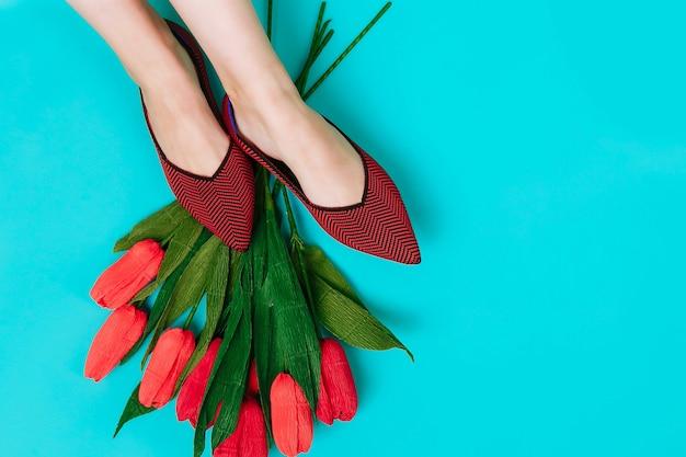 Mooie vrouwelijke benen zijn gekleed in stijlvolle bordeauxrode platte schoenen bourgondische sandalen op een blauwe achtergrond