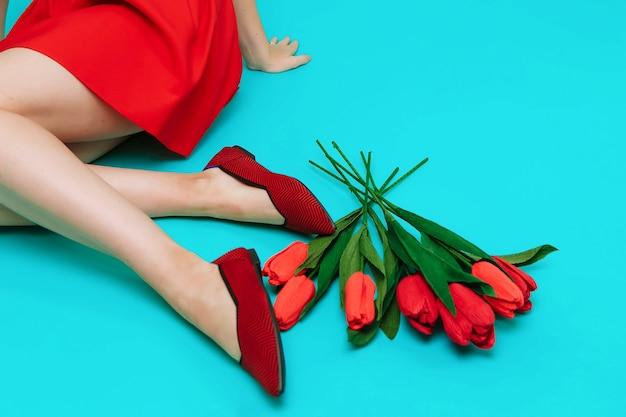Mooie vrouwelijke benen zijn gekleed in stijlvolle bordeauxrode platte schoenen. bourgondische sandalen