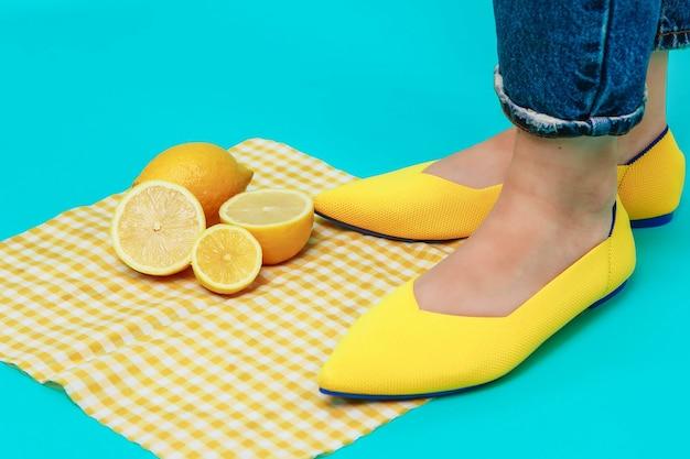 Mooie vrouwelijke benen zijn gekleed in stijlvolle gele schoenen zonder hiel.