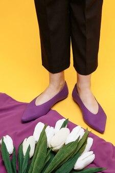 Mooie vrouwelijke benen zijn gekleed in stijlvolle paarse platte schoenen. violette sandalen