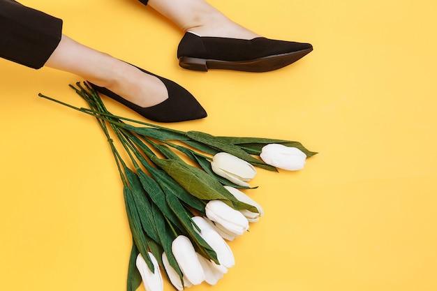 Mooie vrouwelijke benen zijn gekleed in stijlvolle zwarte platte schoenen.