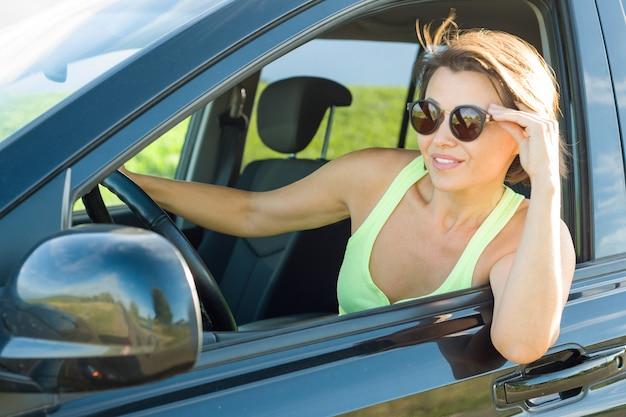 Mooie vrouwelijke bestuurder die terwijl het drijven van zijn auto glimlacht