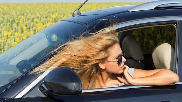 Mooie vrouwelijke bestuurder in auto terugkijkend met haar hoofd uit het raam en haar blonde haren waait in de wind