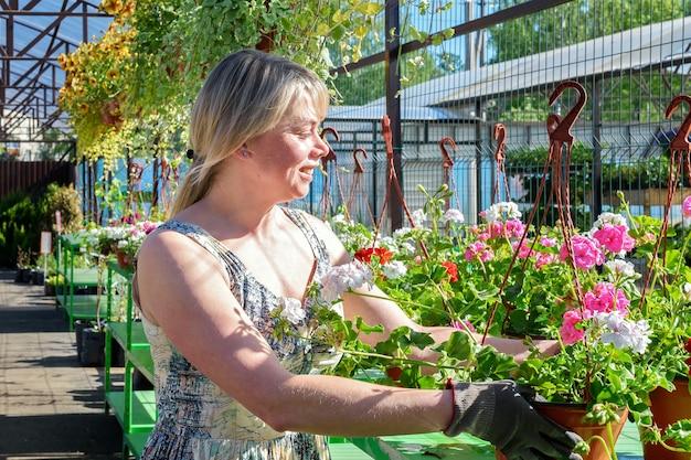 Mooie vrouwelijke bloemist werkt met bloemen in een tuincentrum