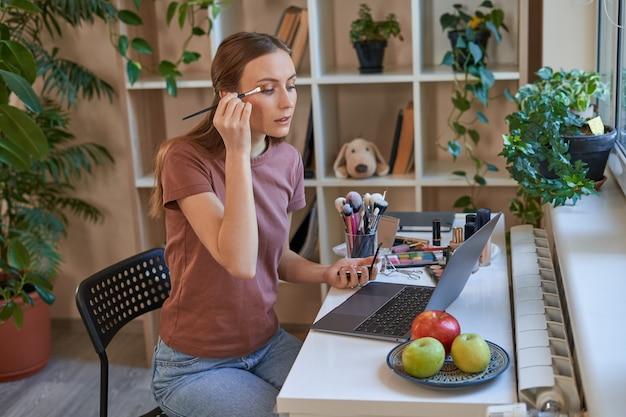 Mooie vrouwelijke blogger die thuis online make-uphandleiding doet