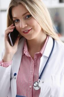 Mooie vrouwelijke blonde arts praten over de telefoon op kantoor vrouw bespreken van de ziekte