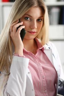 Mooie vrouwelijke blonde arts praten over de telefoon