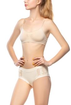 Mooie vrouwelijke buik en borst geïsoleerd op een witte achtergrond.