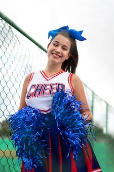 Mooie vrouwelijke cheerleader in schattig uniform