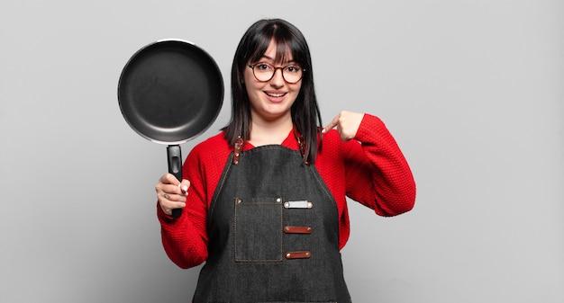 Mooie vrouwelijke chef-kok voelt zich gelukkig, verrast en trots, wijzend naar zichzelf met een opgewonden, verbaasde blik