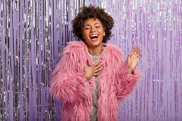 Mooie vrouwelijke clubber die wordt geraakt door mooie woorden van vrienden, wordt gefeliciteerd met haar verjaardag