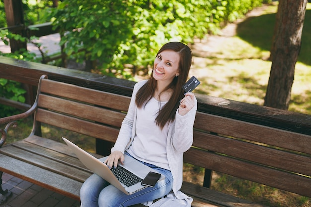 Mooie vrouwelijke creditcard met kopie ruimte te houden. vrouw zittend op een bankje bezig met moderne laptop pc-computer, mobiele telefoon in straat buiten op de natuur. mobiel kantoor. freelance bedrijfsconcept.