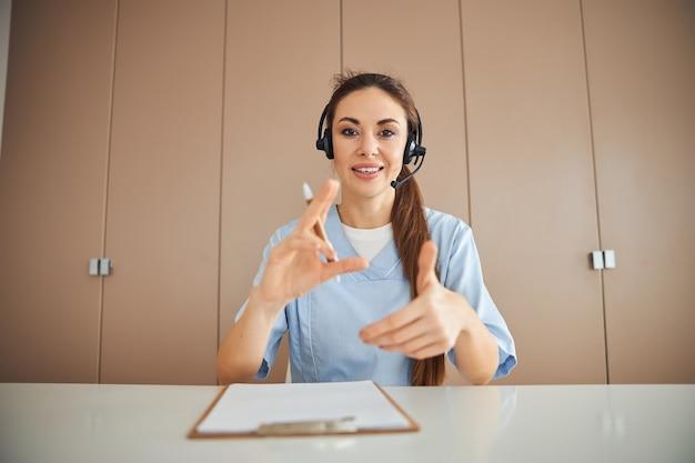 Mooie vrouwelijke dokter die hoofdtelefoon draagt en met haar handen gebaart