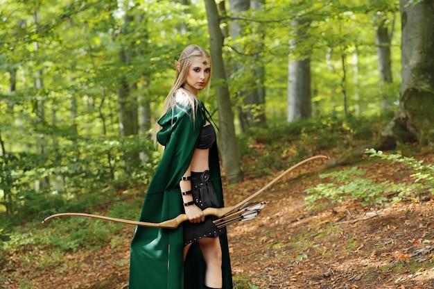 Mooie vrouwelijke elfschutter in de bosjacht met een boog