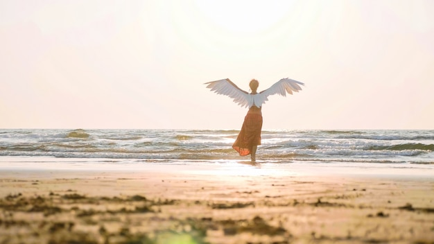 Mooie vrouwelijke engel die blootvoets naar het overzees bij zonsondergang loopt
