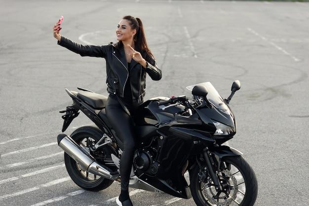 Mooie vrouwelijke fietser maakt selphie foto door smartphone zittend op stijlvolle sport motorfiets