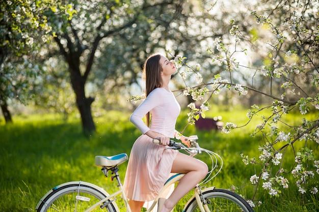 Mooie vrouwelijke fietser met retro fiets in de lentetuin