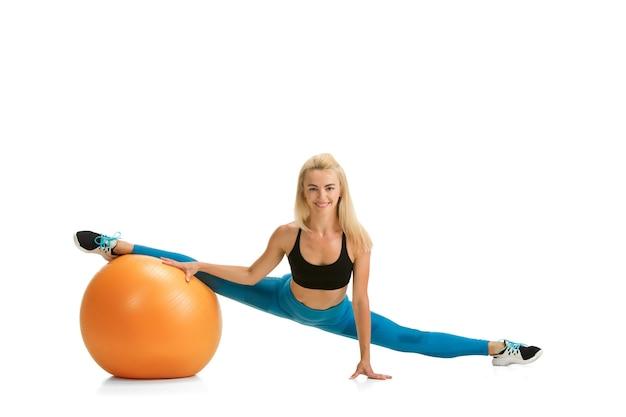 Mooie vrouwelijke fitnesscoach die geïsoleerd op een witte muur oefent