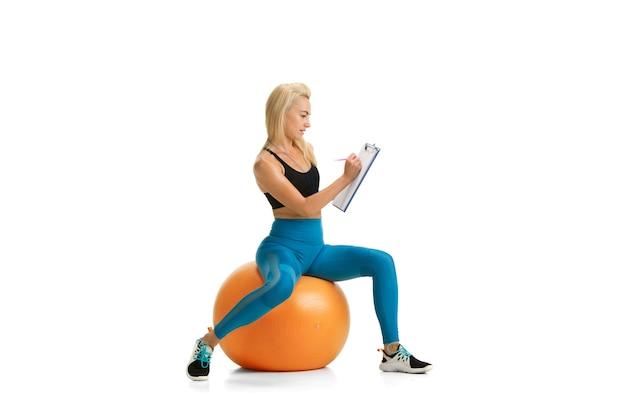 Mooie vrouwelijke fitnesscoach die geïsoleerd op een witte studiomuur oefent